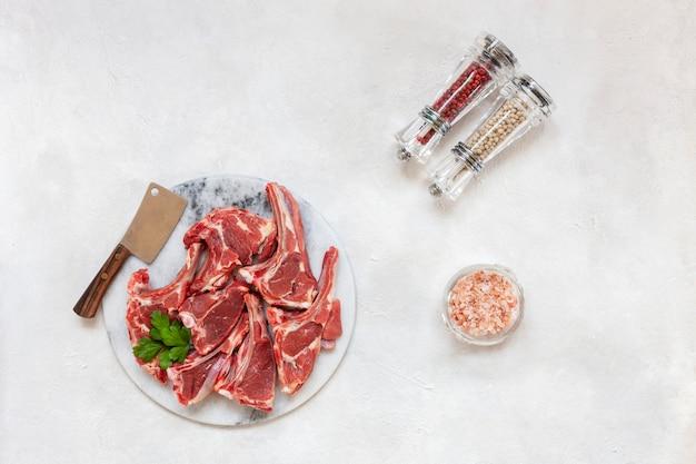 Côtes Et Assaisonnements De Viande D'agneau Fraîche Crue Sur Une Surface Blanche Photo Premium