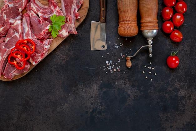Côtes Et Assaisonnements De Viande D'agneau Fraîche Crue Sur Une Surface Sombre Photo Premium