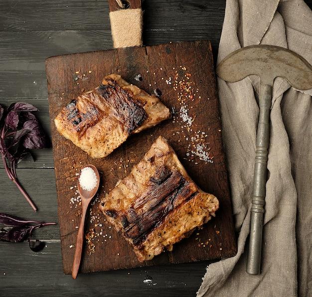 Côtes de porc grillées sur une planche à découper en bois marron Photo Premium