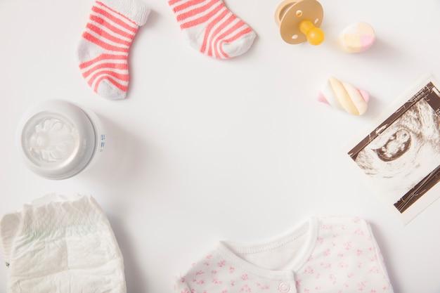 Couche; vêtements pour bébé; guimauve; chaussettes; sucette; image de sonographie et bouteille de lait sur fond blanc Photo gratuit