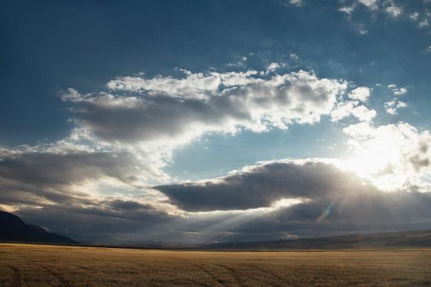 Coucher de soleil dans le désert, les rayons du soleil brillent à travers les nuages. ukok plateau de l'altaï Photo Premium