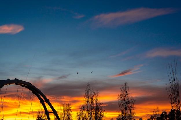 Coucher de soleil dans une ville méditerranéenne avec la silhouette de la structure métallique d'un pont suspendu Photo Premium