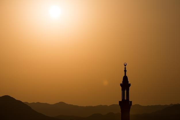 Coucher soleil sur le désert avec mosquée musulman au premier plan Photo Premium
