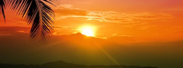 Coucher de soleil heure dorée ciel avec soleil sur montagne et feuille de palmier Photo Premium