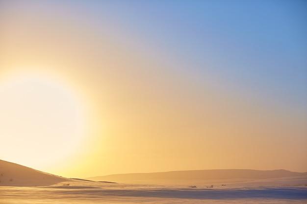 Coucher de soleil d'hiver sur fond de montagnes enneigées Photo Premium
