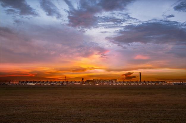 Coucher de soleil à la lumière sur la pelouse dorée de l'aéroport de bangkok, en thaïlande. Photo Premium