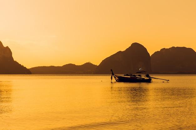 Coucher de soleil sur la mer océan calme avec la silhouette du bateau de pêche et paysage de montagne Photo Premium
