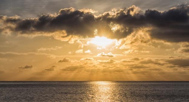 Coucher de soleil sur la mer avec les rayons du soleil à travers les nuages Photo Premium