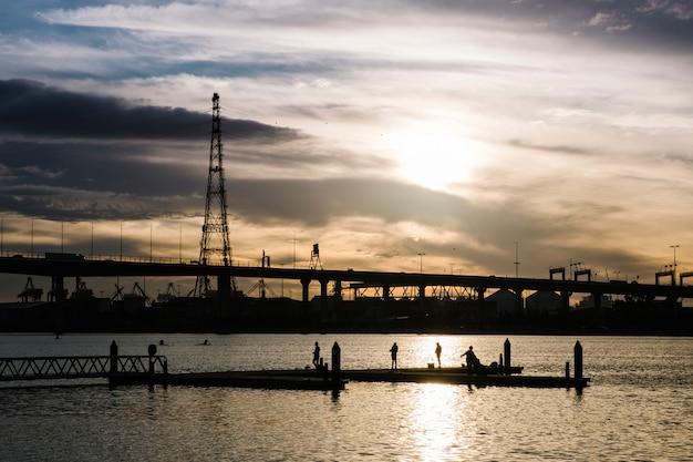 Coucher de soleil en mer et la ville Photo gratuit