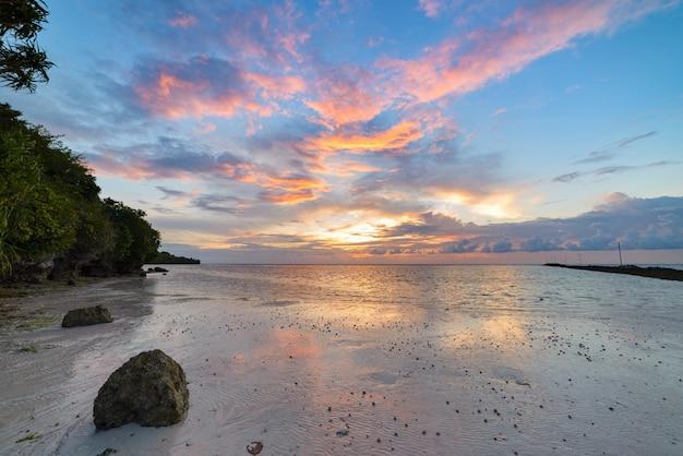 Coucher de soleil sur la plage du désert tropical, reflet des récifs coralliens, destination de voyage, indonésie wakatobi Photo Premium