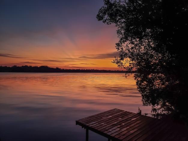 Coucher de soleil sur la rivière en été et jetée en bois Photo Premium