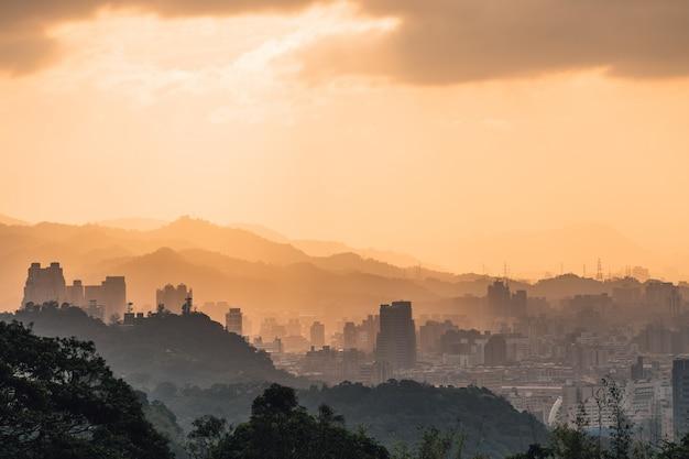 Couches du paysage urbain de taipei et des montagnes avec la lumière du soleil quand le soleil se couche. Photo Premium
