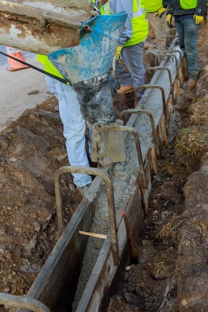 Coulage du ciment pendant la construction du camion malaxeur à béton voiture. focus sélectif. Photo Premium