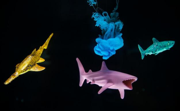 Couleur Acrylique Se Dissolvant Dans L'eau Avec Des Requins Jouets Photo gratuit