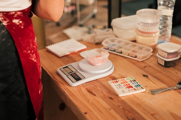 Couleur céramique sur le bol sur l'échelle de mesure sur le bureau en bois Photo gratuit