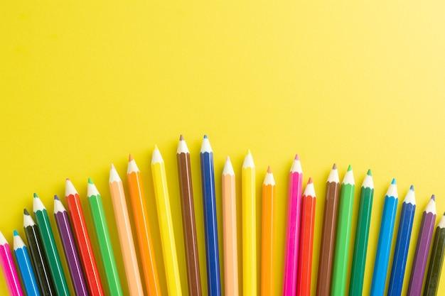Couleur de crayons sur fond de papier jaune. Photo Premium