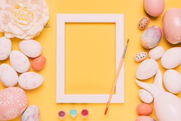 Couleur de peinture; pinceau; cadre de bordure blanche; oeufs de rose et de pâques sur fond jaune Photo gratuit