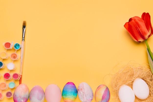 Couleur de peinture; pinceau; tulipe rouge; nid et oeufs de pâques sur fond jaune Photo gratuit