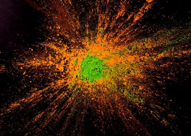 Couleur de poudre verte sur la couleur orange sur le fond noir Photo gratuit