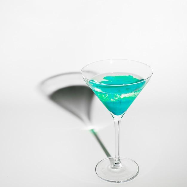 Couleur turquoise diffuse dans l'eau à l'intérieur d'un verre à martini avec ombre sur fond blanc Photo gratuit