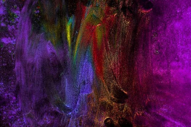 Couleurs holi multicolores bavées avec la main sur fond noir Photo gratuit