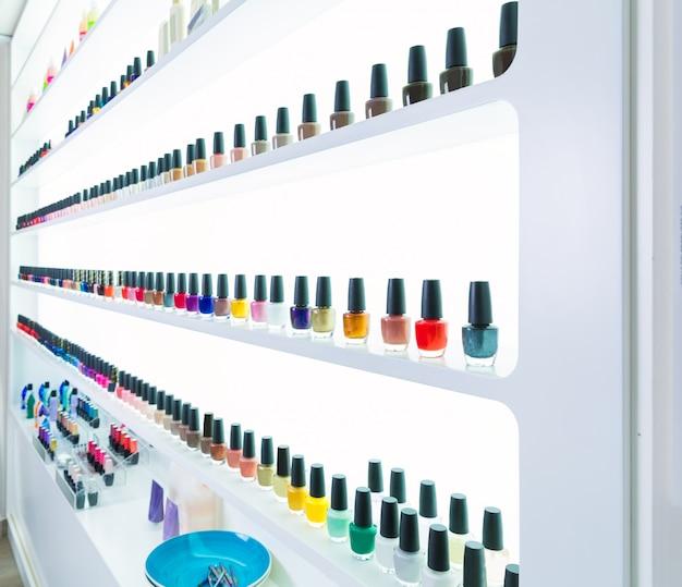 Couleurs de vernis à ongles colorés dans une rangée au salon des ongles sur blanc Photo Premium