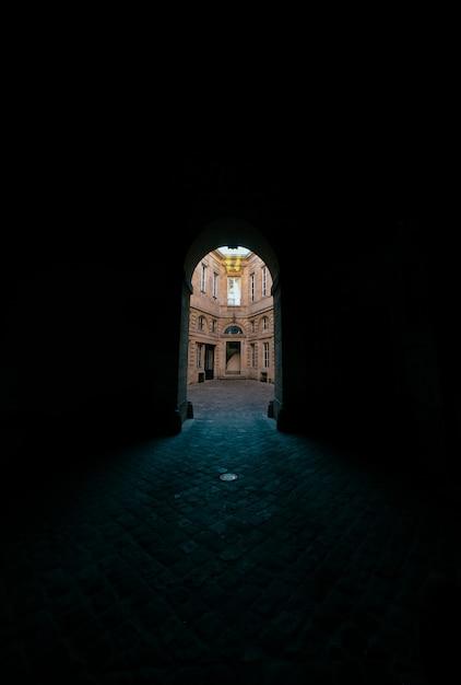 Couloir Sombre Avec Porte Voûtée Avec Vue Sur Un Bâtiment En Béton Photo gratuit