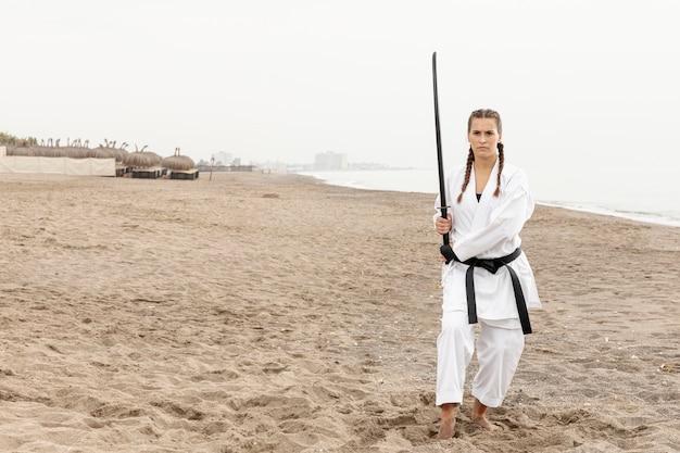 Coup complet femme en costume d'arts martiaux en plein air Photo gratuit