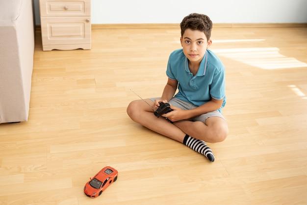 Coup complet garçon jouant avec une voiture électrique Photo gratuit