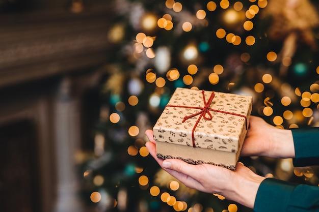Coup hirizontal de belle boîte cadeau emballée dans les mains de la femme contre un arbre décoré de noël ou du nouvel an Photo Premium