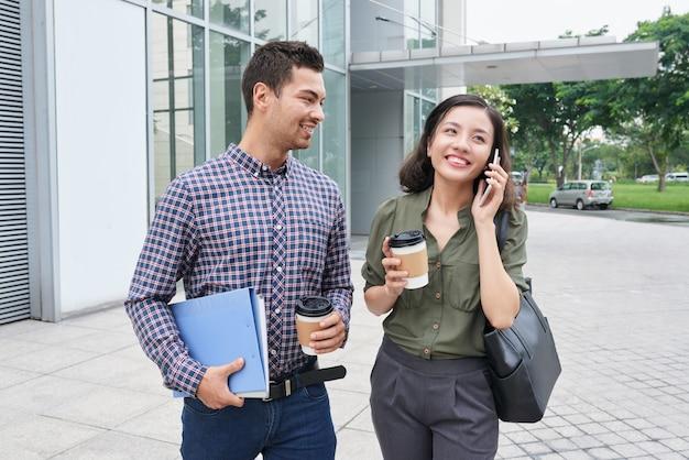 Coup de longueur moyenne de deux collègues debout avec des tasses de café à emporter à l'extérieur, une femme passe un appel téléphonique Photo gratuit