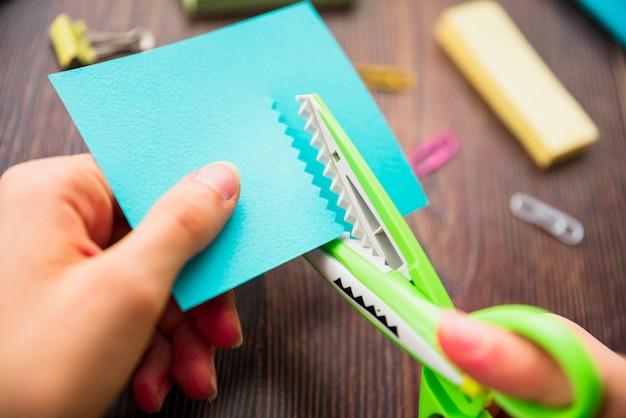 Coup de macro de la main d'une personne coupant du papier turquoise avec des ciseaux en zigzag Photo gratuit