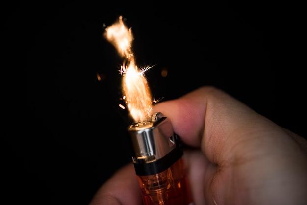 Coup de macro de la main tenant un briquet Photo gratuit