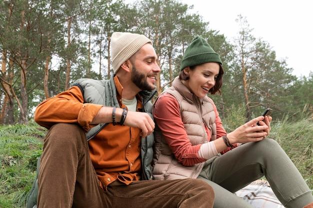 Coup De Milieu Heureux Couple Assis Sur L'herbe Et Regardant Le Téléphone Photo gratuit