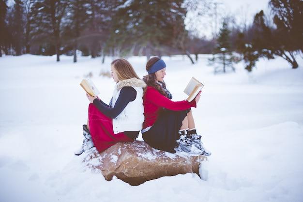 Coup De Mise Au Point Peu Profonde De Deux Femmes Assises Sur Le Rocher Dos à Dos Tout En Lisant La Bible Photo gratuit