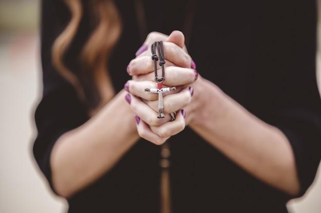 Coup De Mise Au Point Peu Profonde D'une Femme Portant Une Chemise Noire Tout En Tenant Une Croix Dans Sa Main Photo gratuit