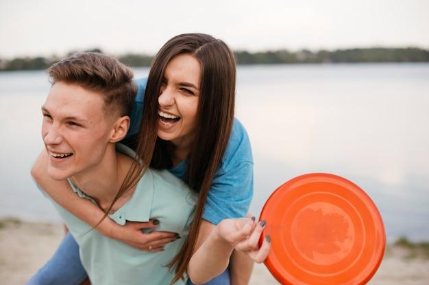 Coup moyen adolescents riant avec frisbee Photo gratuit