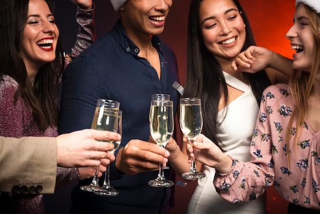 Coup moyen d'amis souriants portant un toast Photo gratuit