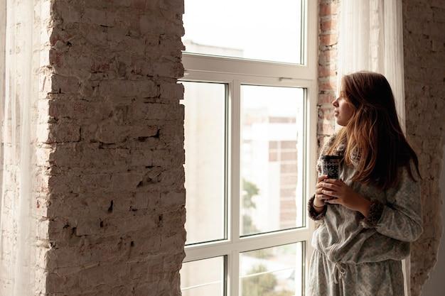 Coup moyen belle fille regardant par la fenêtre Photo gratuit