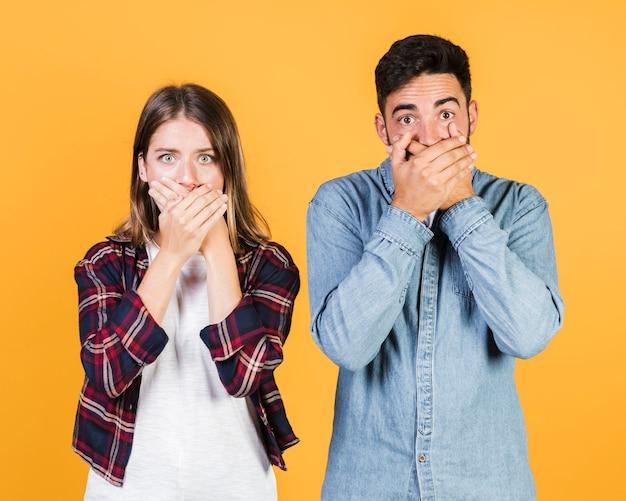 Coup moyen couple couvrant leur bouche Photo gratuit