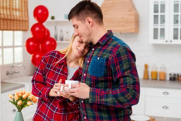 Coup moyen couple heureux dans la cuisine avec des tasses à café Photo gratuit