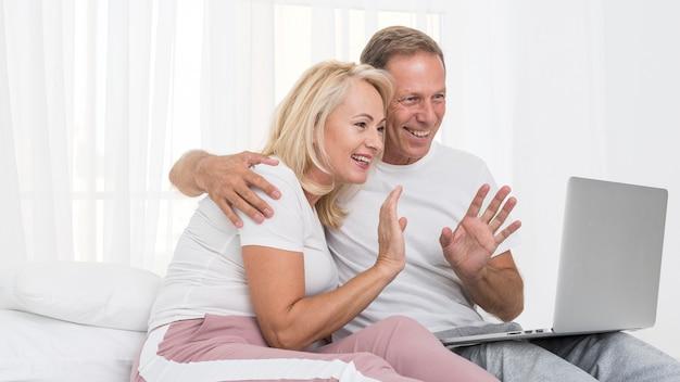 Coup Moyen Couple Heureux Avec Ordinateur Portable En Agitant Photo gratuit