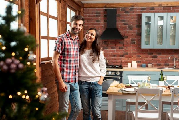 Coup moyen couple heureux posant dans la cuisine Photo gratuit