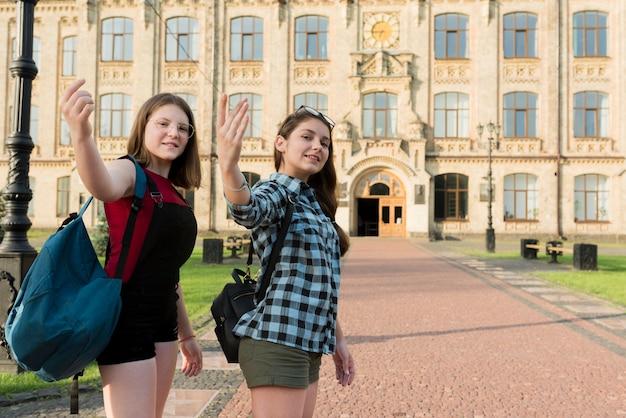 Coup moyen de deux lycéennes regardant la caméra Photo gratuit