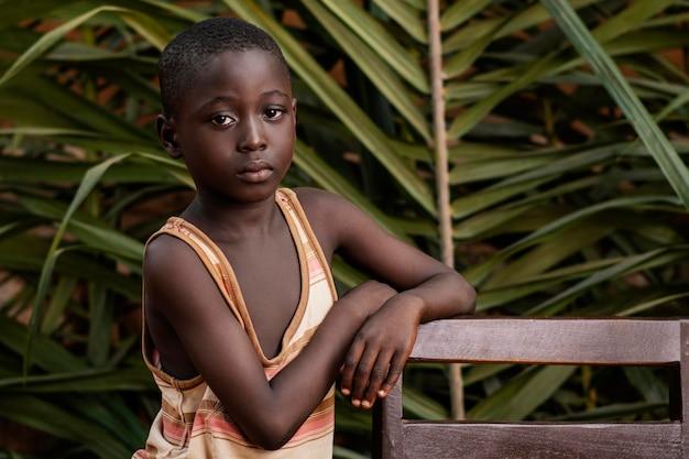 Coup Moyen Enfant Posant Avec Chaise Photo gratuit