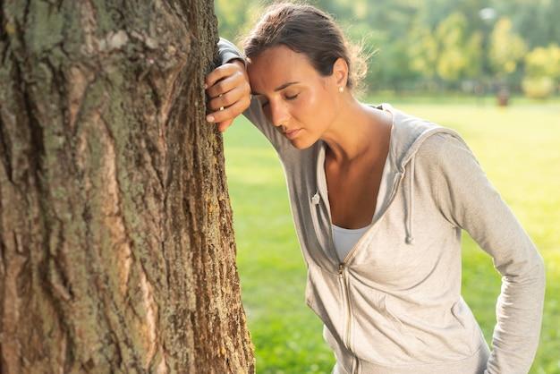 Coup moyen femme au repos près d'un arbre Photo gratuit