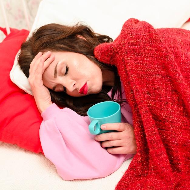 Coup moyen femme ayant mal à la tête tout en restant au lit Photo gratuit