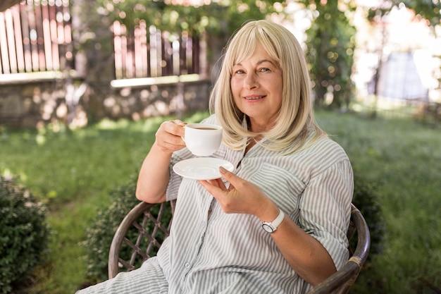 Coup Moyen Femme Buvant Du Café Photo gratuit