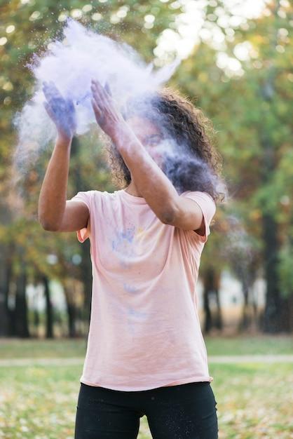 Coup moyen de femme créant de la poussière bleue Photo gratuit