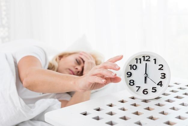 Coup Moyen Femme Dormant Avec Une Horloge Photo gratuit